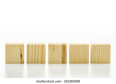 Row of five blank wooden blocks on a white background with copyspace for your text, letters or numbers.