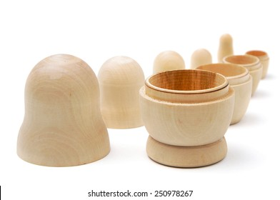 Row of five disassembled wooden matryoshkas on white background