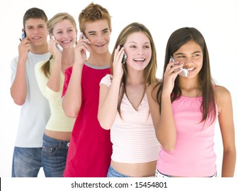 Row of five friends on cellular phones smiling