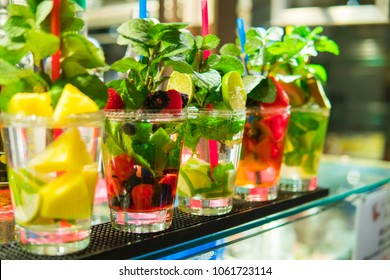 Row of five glasses with fruit mojito coctails