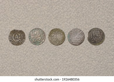 a row of five old silver Polish medieval coins lie on a gray table - Shutterstock ID 1926480356