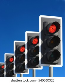 ROW OF FIVE ROAD TRAFFIC LIGHTS SHOWING RED WITH BLUE SKY