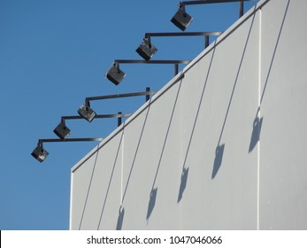 Row of floodlights on industrial building with shadows