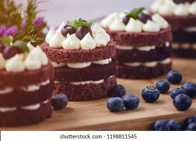 Row of four brown cakes with blueberry on top placing together pink flower and berry as decorated item on the wooden plate
