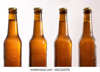 Row of four closed glass bottles with fresh beer on white background. Horizontal composition. Front view.