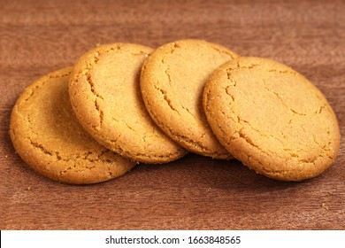 A row of four ginger biscuits on a dark wooden background