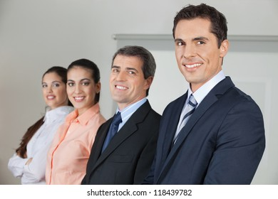 Row of four happy businesspeople in the office