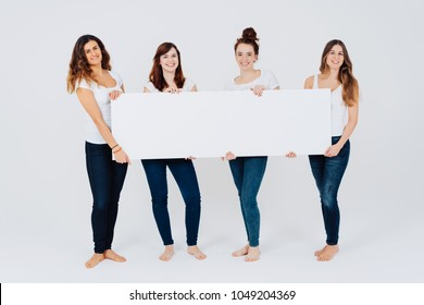 Row of four happy friendly women in casual denim jeans and bare feet standing with a panoramic banner blank white sign in their hands smiling isolated on white