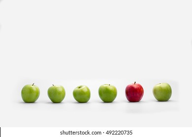 Row of fresh green apples with a single red one isolated on white with copy space conceptual of individualism, diversity, originality and choice