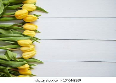 Row of fresh Yellow tulips on white wooden table. Top view, flat lay with space for you text.