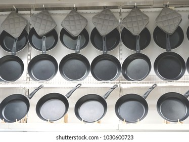 Row of frying pan on display at kitchen utilities section in supermarket
