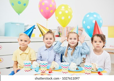 Row of funny children in birthday caps sitting by festive table with pieces if cake, drinks and cookies