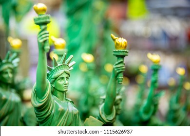 Row with generic Statue of Liberty statues (selective focus) sold as souvenirs in a NYC shop.
