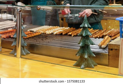 Row of German wurst sausages on grill for selling at Christmas market in Germany. Selective focus.