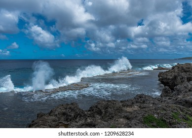 A row of geysers shoots upward as the  tide rolls in and forces water through blowholes.