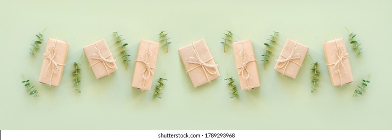 Row gift boxes wrapped in kraft paper, tied with jute twine and natural twigs of eucalyptus on green background. Holiday concept Top view Flat lay Template for your design Banner.