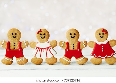 Row of gingerbread men against a background of Christmas lights