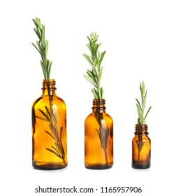 Row of glass bottles with rosemary on white background