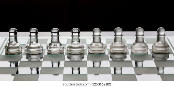 Row of glass chess pawns on the board with black and white shade