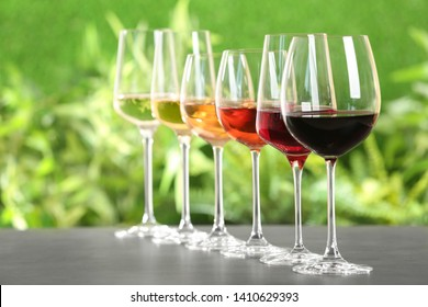 Row of glasses with different wines on grey table against blurred background. Space for text