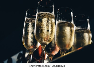 a row of glasses filled with champagne are lined up ready to be served