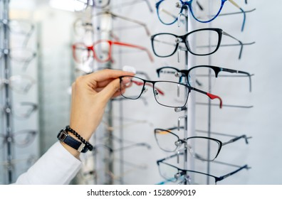 Row of glasses at an opticians. Eyeglasses shop. Stand with glasses in the store of optics. Woman's hand chooses glasses. Presenting spectacles.