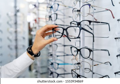 Row of glasses at an opticians. Eyeglasses shop. Stand with glasses in the store of optics. Woman chooses spectacles. Eyesight correction. - Shutterstock ID 1553934869