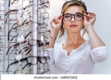 Row of glasses at an opticians. Eyeglasses shop. Stand with glasses in the store of optics. Woman chooses spectacles. Eyesight correction. - Shutterstock ID 1680413602