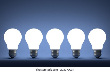 Row of glowing tungsten light bulbs on blue textured background