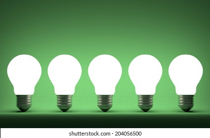 Row of glowing tungsten light bulbs on green textured background
