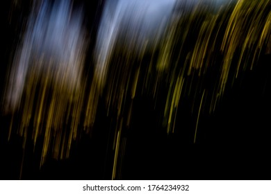 Row of golden light streaks falling downwards, with light / off-white tones above, and dark / blacked-out area below - abstract motion-blurred background / texture