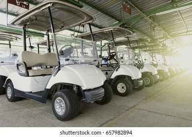 A row of golf carts on a golf course parking area.