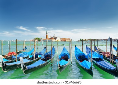 A row of gondolas parked beside the Riva degli Schiavoni in Venice, Italy. View of the Venetian Lagoon. The Church of San Giorgio Maggiore on island of the same name is visible in background.