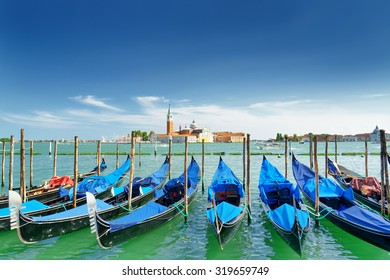 A row of gondolas parked beside the Riva degli Schiavoni in Venice, Italy. Scenic view the Venetian Lagoon at summer time. The Church of San Giorgio Maggiore on island is visible in background.