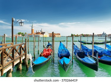 A row of gondolas parked at pier beside the Riva degli Schiavoni in Venice, Italy. Scenic view of the Venetian Lagoon. The Church of San Giorgio Maggiore on island is visible in background.