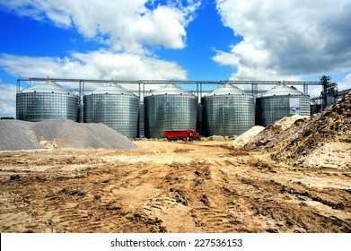 A row of granaries against the blue sky. Silos for wheat storage and drying. A red lorry in front of the granaries.