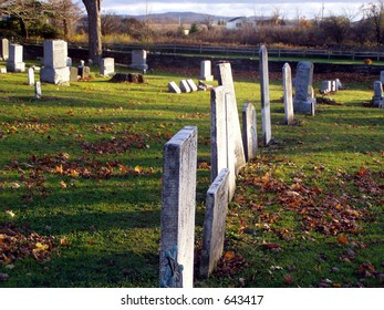 row of grave stones in a cemetery in the fall.