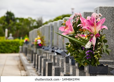 Row of gravestones in a typical Japanese cemetery, with flowers, selective focus