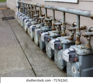 Row gray gas meters at an apartment complex