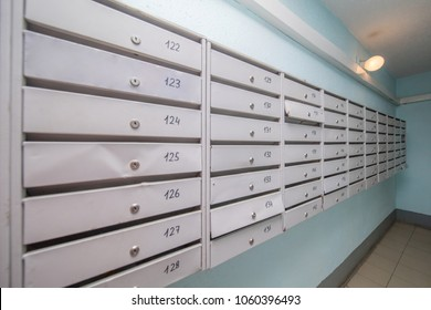 row of gray mailboxes in corridor of apartment building