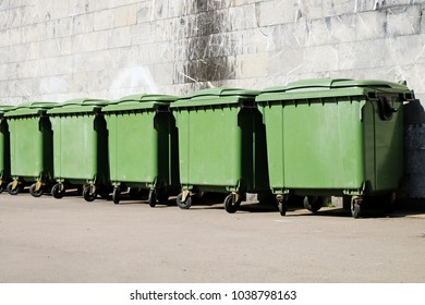 A row of green garbage containers on the city street.