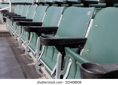 Row of green stadium seats folded up.