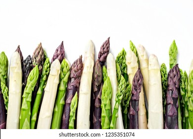 Row green, white and lilac Asparagus as close-up in a row with copy space on top – isolated