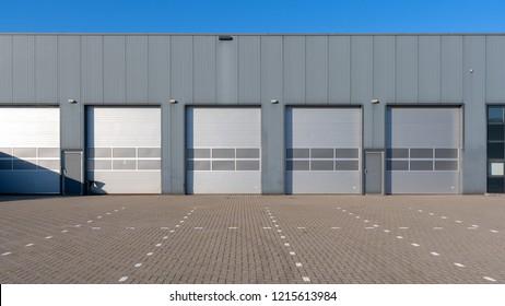 Reihe von grauen Industrieeinheiten mit Rollladentüren.