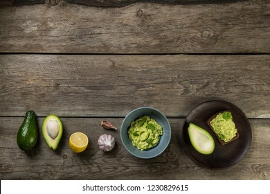 Row of guacamole ingridients: avocado, lemon, garlic, plate, bread