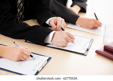 Row of hands filling in a form