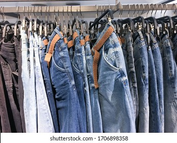 Row of hanged blue jeans. Jeans store in a shopping center. Denim sales. Blue pants