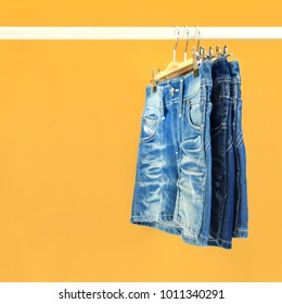 Row of hanged blue jeans with yellow background