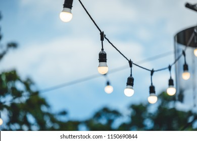 Row of hanging summer terrace lights during evening, small outdoor light bulbs