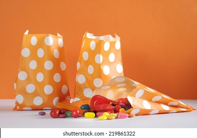 Row of Happy Halloween orange polka dot trick or treat paper bags with multi-color candy against and orange and white background.